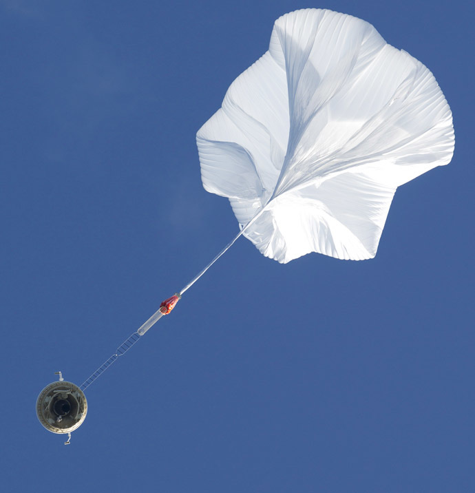 A high altitude balloon lifts a saucer-shaped test vehicle, which holds equipment for landing large payloads on Mars, at the U.S. Navy's Pacific Missile Range Facility in Kauai, Hawaii June 28, 2014. (Reuters/Marco Garcia)