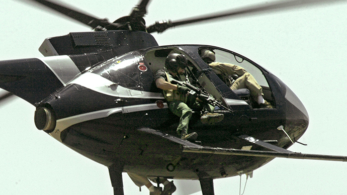 ARCHIVE PHOTO: Members of the US Blackwater private security company fly a Hughes 500 helicopter over the Tigris river in Baghdad, during a patrol 05 May 2004 (AFP Photo / Marwan Namaani)