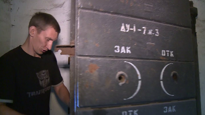 Vadim Streltsov, local resident, opens a door to the bomb shelter, Lugansk, eastern Ukraine (screenshot from RT video)