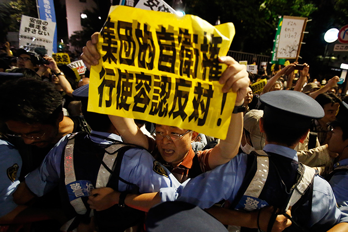 A protester holding a placard shouts slogans at a rally against Japan's Prime Minister Shinzo Abe's push to expand Japan's military role as police officers refrain him in front of Abe's official residence in Tokyo June 30, 2014 (Reuters / Yuya Shino)