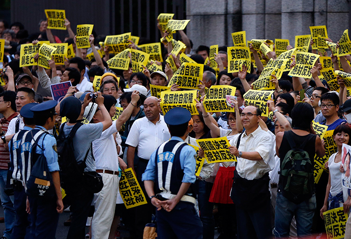 Protesters holding placards shouts slogans as they gather at a rally against Japan's Prime Minister Shinzo Abe's push to expand Japan's military role while police officers stand guard in front of Abe's official residence in Tokyo June 30, 2014 (Reuters / Issei Kato)