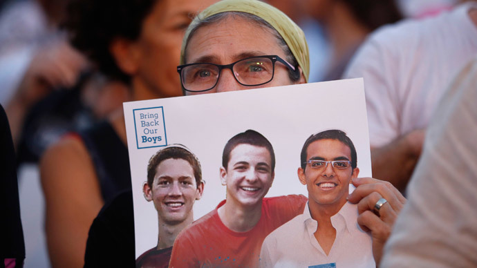 An Israeli woman holds a sign with images of three missing Israeli teenagers, at a rally in Rabin Square in the coastal city of Tel Aviv.(Reuters / Baz Ratner)