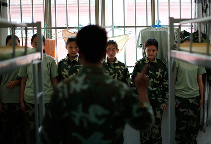 An instructor who is an ex-soldier talks to female students in their dormitory at the Qide Education Center in Beijing June 10, 2014 (Reuters / Kim Kyung-Hoon)