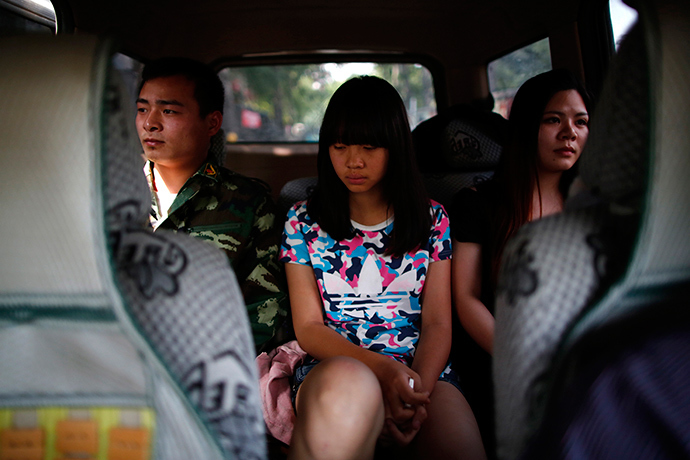 A female teacher and an instructor who is an ex-soldier, escort a girl in a car as they take her to the Qide Education Center at the request of her parents, in Beijing May 22, 2014 (Reuters / Kim Kyung-Hoon)