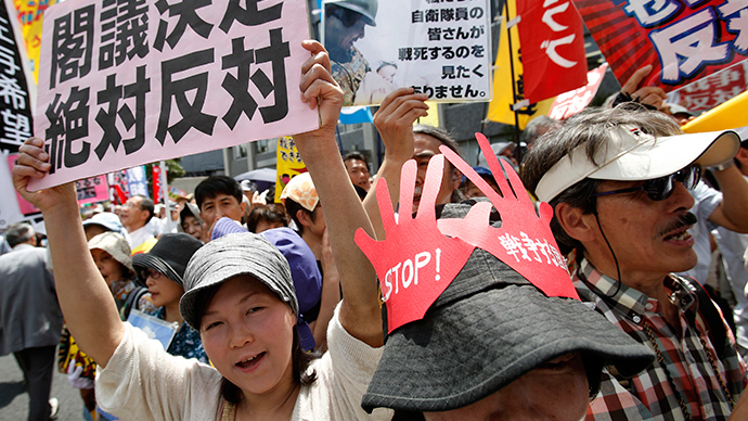 Protesters holding placards shout slogans at a rally against Japan's Prime Minister Shinzo Abe's push to expand Japan's military role in front of Abe's official residence in Tokyo July 1, 2014 (Reuters / Yuya Shino)