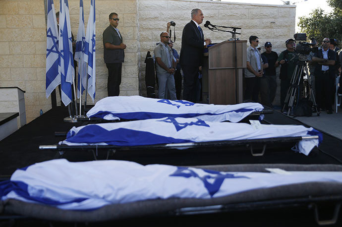 Israeli Prime Minister Benjamin Netanyahu (Background) delivers a speech next to the bodies of Gilad Shaer and Naftali Frenkel, both 16, and 19-year-old Eyal Ifrach, all three wrapped in their national flag, as he attends their funeral on July 1, 2014 in the cemetery of Modiin in central Israel. (AFP Photo / Baz Ratner)