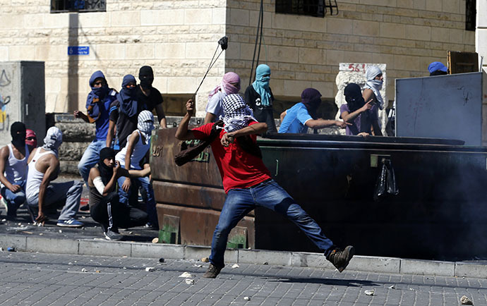 A Palestinian uses a sling to hurl a stone towards Israeli police during clashes in Shuafat, an Arab suburb of Jerusalem July 2, 2014. (Reuters / Baz Ratner)