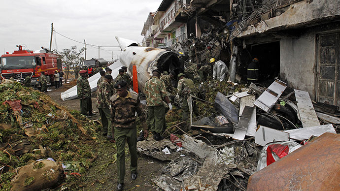 Security personnel stand at the site of the wreckage of a cargo plane that crashed into a commercial building on the Utawala estate on the outskirts of Kenya's capital Nairobi, July 2, 2014. (Reuters / Thomas Mukoya)