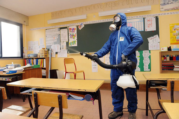 A man sprays a disinfectant against the swine flu virus on November 18, 2009 in a classroom of the Georges Brassens school in Baillargues, southern France. (AFP Photo / Pascal Guyot)