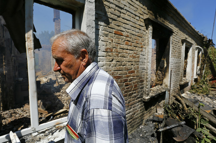 Local resident Viktor Shevchenko walks outside a building damaged by a recent shelling in the Ukrainian eastern city of Slaviansk July 1, 2014. (Reuters/Shamil Zhumatov)