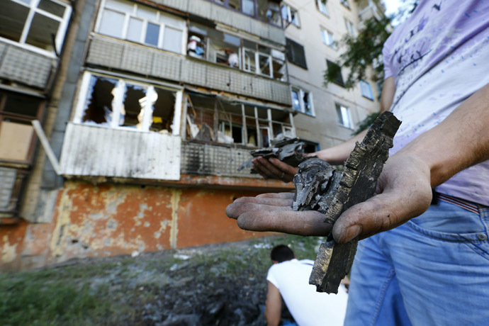 A local resident holds fragments of shrapnel near an apartment damaged by shelling in Slaviansk in eastern Ukraine June 29, 2014. (Reuters/Shamil Zhumatov)