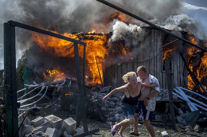 Local residents escape from a fire in the house destroyed in the Ukrainian armed forces' air attack on the village of Luganskaya on July 2, 2014 (RIA Novosti/Valeriy Melnikov)