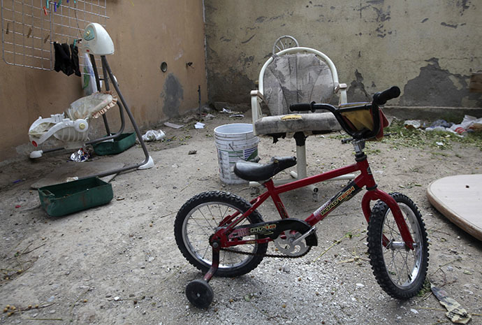 An abandoned bicycle for children, a baby swing and rubbish are seen in the back patio of a house seized by authorities in Ciudad Juarez May 23, 2014. (Reuters / Jose Luis Gonzalez)