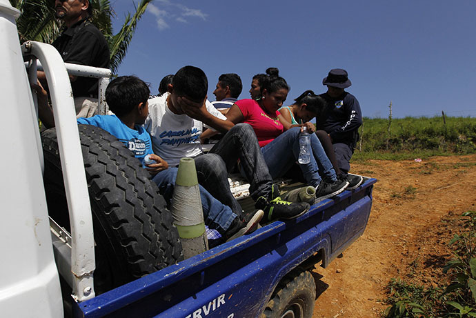 Unaccompanied minors and a family sit in the bed of a police truck after being detained for the lack of identity documents at a porous border known as La Montanita in the small village of Suyapa, on the border of Honduras with Guatemala June 20, 2014. (Reuters / Jorge Cabrera)
