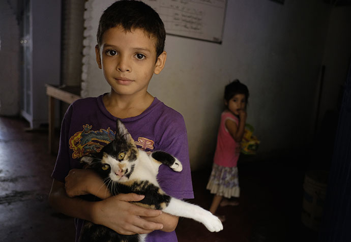 A Honduran child, who will be accompanied by his family when they travel to reach northern Mexico or the U.S., holds a cat as he poses for a picture at the Todo por ellos (All for them) immigrant shelter in Tapachula, Chiapas, in southern Mexico, June 26, 2014. (Reuters / Jorge Lopez)