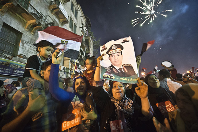 People celebrate at Tahrir Square with a portrait of Army chief Abdel Fattah al-Sisi after a broadcast confirming that the army will temporarily be taking over from the country's first democratically elected president Mohamed Morsi on July 3, 2013 in Cairo. (AFP Photo / Khaled Desouki)