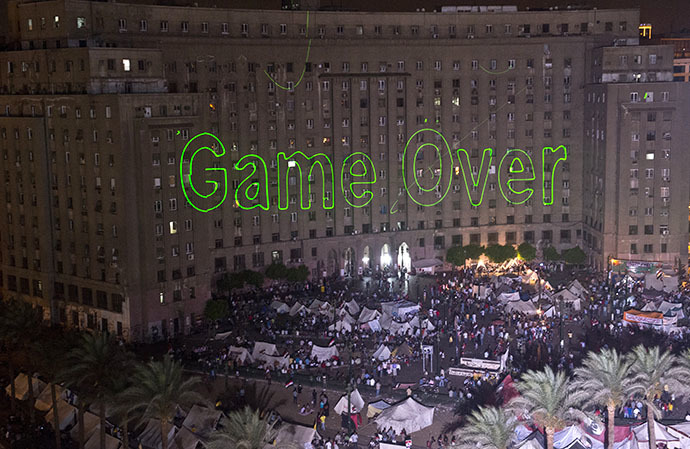 """Egyptian protesters calling for the ouster of President Mohamed Morsi gather in Cairo's landmark Tahrir Square on July 2, 2013 as laser lights (L) directed at the government building spell """"Game Over."""" (AFP Photo / Khaled Desouki)"""