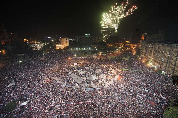 Fireworks light up the sky as Hundreds of thousands of Egyptians celebrate after Egytptian Defense Minister Adel Fattah al-Sisi's speech announcing The Egyptian army toppling Islamist President Mohamed Morsi in Egypt's landmark Tahrir square on July 3, 2013 in Cairo, Egypt. (AFP Photo / Gianluigi Guercia)