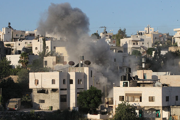 Smoke rises from the home of Ziad Awwad, 42, and his son Ezzedine Awwad, 18, after it was destroyed by the Israeli military, in the village of Idnah, close to the southern West Bank city of Hebron, on July 2, 2014. (AFP Photo / Hazem Bader)
