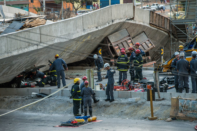 Firefighters and policemen work at the site where several vehicles were crushed by a viaduct that collapsed in Belo Horizonte, Brazil, on July 3, 2014. (AFP Photo/Pedro Duarte)
