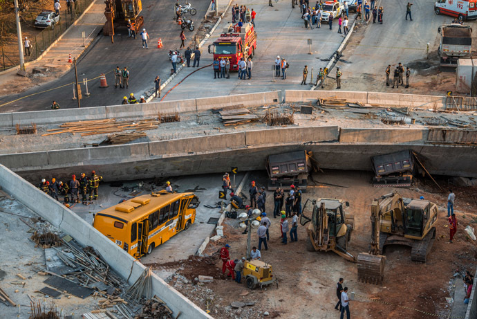 Firefighters and policemen work at the site where a bus and trucks were crushed by a viaduct that collapsed in Belo Horizonte, Brazil, on July 3, 2014 (AFP Photo/Pedro Duarte)