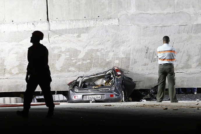A car is trapped underneath a bridge that collapsed while under construction in Belo Horizonte July 3, 2014. (Reuters/Ivan Alvarado)