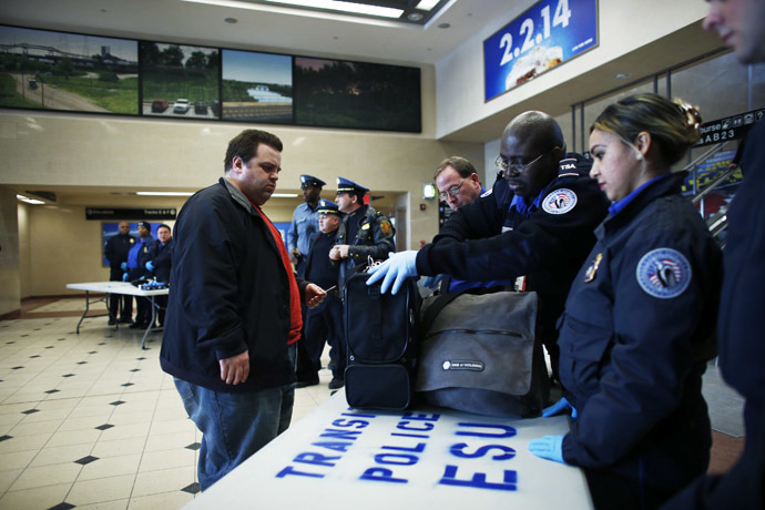 Members of the Transportation Security Administration (TSA) check a passenger's bags with N.J. Transit Police to secure mass transit for the Super Bowl XLVIII, in Secaucus, New Jersey January 31, 2014. (Reuters/Eduardo Munoz)