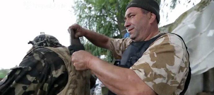 National Guard fighter taking damaged plate from bullet-proof vest. Still from Hromadske.tv video
