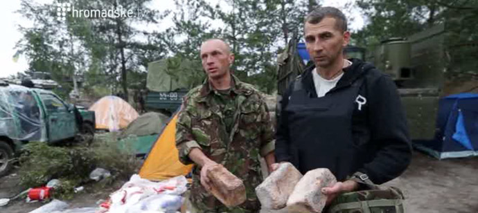 National Guard fighters showing mould-covered bread loaves. Still from Hromadske.tv video