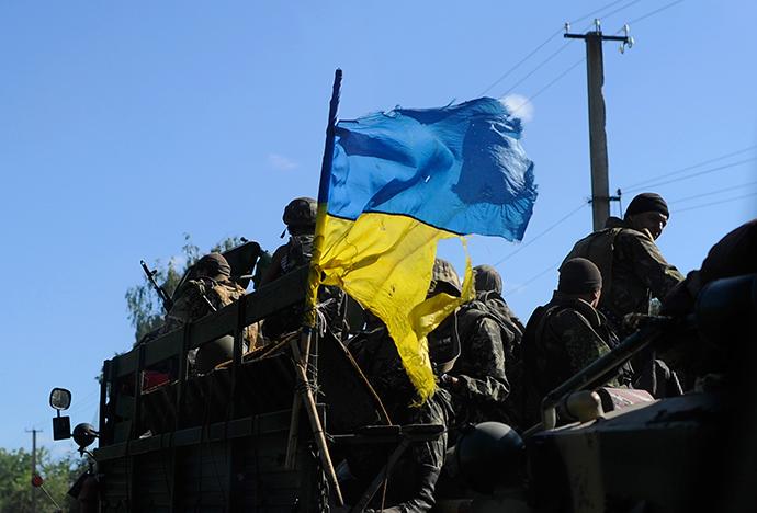 Soldados ucranianos conduzir um veículo militar com uma bandeira rasgada ucraniano em um posto de controle perto Slavyansk no leste da Ucrânia 03 de julho de 2014 (Reuters / Andrew Kravchenko)