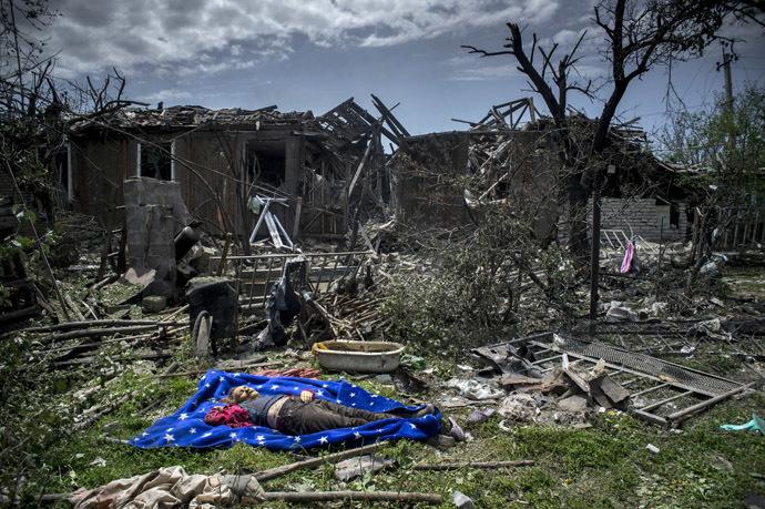 O corpo de um morador morto em ataque aéreo das forças armadas ucranianas na aldeia de Luganskaya em 02 de julho de 2014 (RIA Novosti / Valeriy Melnikov)