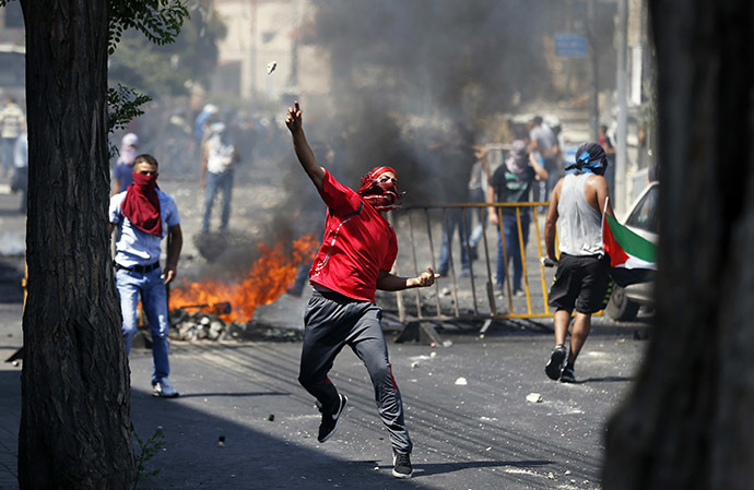 A Palestinian throws a stone during clashes with Israeli police after prayers on the first Friday of the holy month of Ramadan in the East Jerusalem neighbourhood of Wadi al-Joz July 4, 2014. (Reuters / Baz Ratner)
