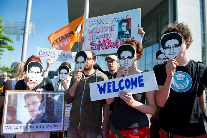 Activists of German Pirate party wearing mask featuring US intelligence leaker Edward Snowden attend a rally on May 22, 2014 in front of Bundestag, German parliament, in Berlin. (AFP Photo/DPA)