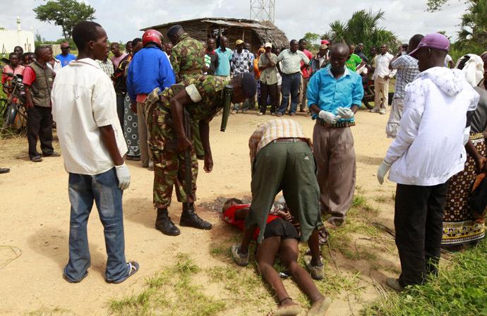Policemen recover the slain body of a man killed when gunmen attacked Hindi village, near Kenya's coastal town of Lamu, July 6, 2014. (Reuters/Joseph Okanga)