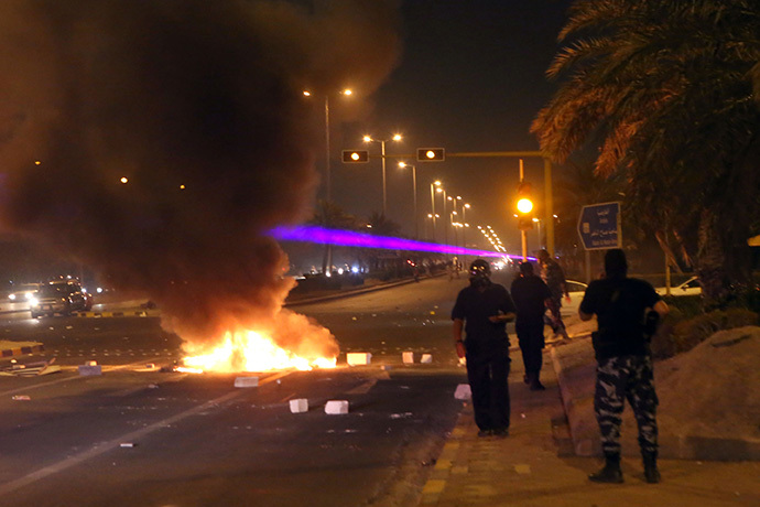 Kuwaiti security forces arrive at the scene as tires are burning during a demonstration of supporters of Kuwaiti opposition leader and former MP Mussallam al-Barrak to ask for his release on July 6, 2014 in Kuwait City (AFP Photo / Yasser Al-Zayyat)