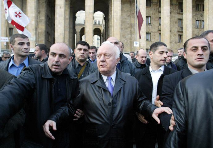 Georgian President Eduard Shevarnadze walks surrounded by bodyguards outside Parliament building in Tbilisi, 09 November 2003. (AFP Photo/Victor Drachev)