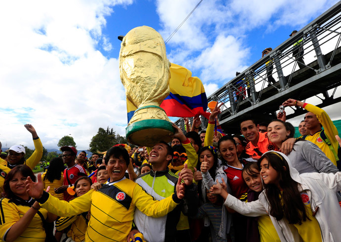 Colombian fans pose with a big replica of the World Cup 2014 trophy as they wait for the arrival of Colombia's national soccer team in Bogota July 6, 2014.(Reuters / Jose Miguel Gomez)
