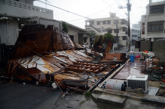 A wooden house collapsed during strong winds in Naha on Japan's southern island of Okinawa on July 8, 2014 (AFP Photo / Jiji Press)