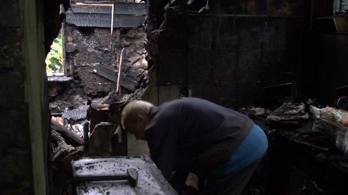 A local resident in destroyed house in Lugansk (screenshot from RT)