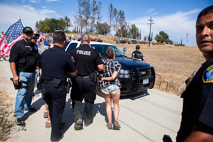 A protester is handcuffed and placed in a police car after a scuffle broke out before the possible arrivals of undocumented migrants who may be processed at the Murrieta Border Patrol Station in Murrieta, California July 4, 2014 (Reuters / Sam Hodgson)
