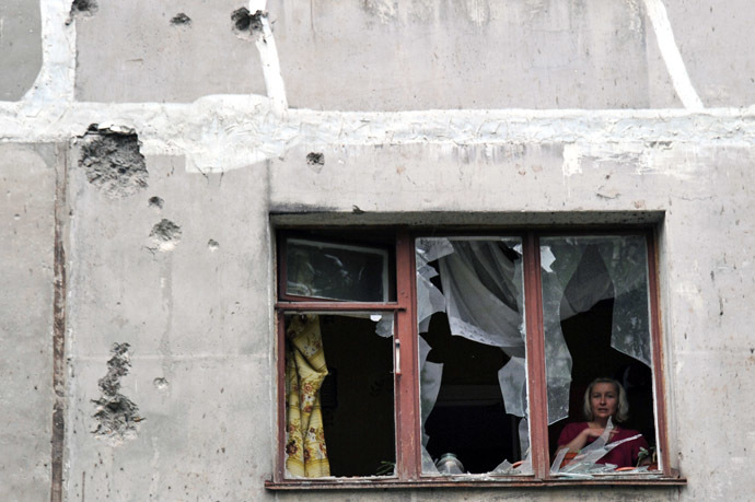 A resident is seen through her window on July 9, 2014 inside her apartment, in a building damaged the day before by Ukrainian forces' mortar fire, in Lugansk, eastern Ukraine. (AFP Photo)
