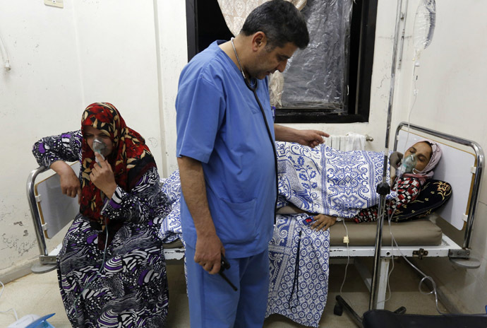 Women, affected by what activists say was a gas attack, receive treatment inside a makeshift hospital in Kfar Zeita village in the central province of Hama May 22, 2014. (Reuters/Badi Khlif)