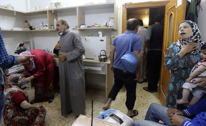 A woman (L), affected by what activists say was a gas attack, breathes through an oxygen mask inside a hospital in Kfar Zeita village in the central province of Hama May 19, 2014. (Reuters/Badi Khlif)
