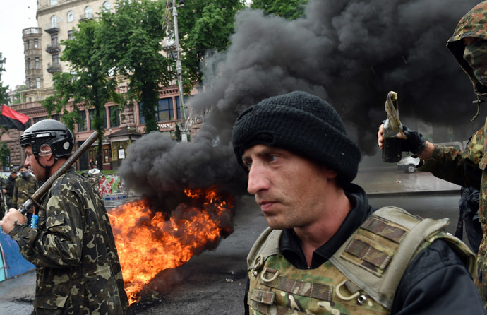 "Protesters from Kiev's Independence Square, the so-called ""Maidan"", hold a metal bar and a petrol bomb as they burn tyres to protect their barricades from being dismantled by communal services on May 31, 2014 in the centre of Kiev. (AFP Photo)"