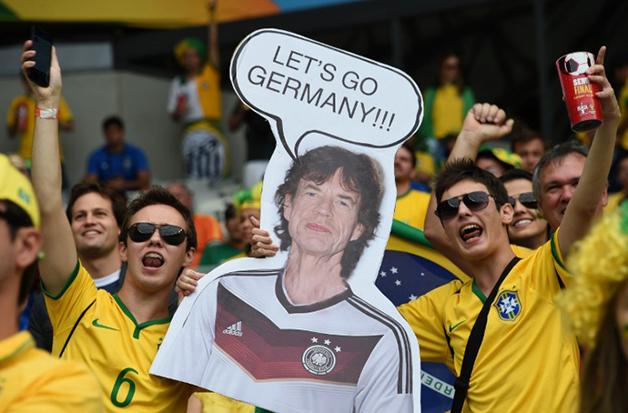Brazilian fans hold a cardboard cutout of The Rolling Stones' Mick Jagger before the semi-final football match between Brazil and Germany at The Mineirao Stadium in Belo Horizonte during the 2014 FIFA World Cup on July 8, 2014. (AFP Photo / Vanderlei Almeida)