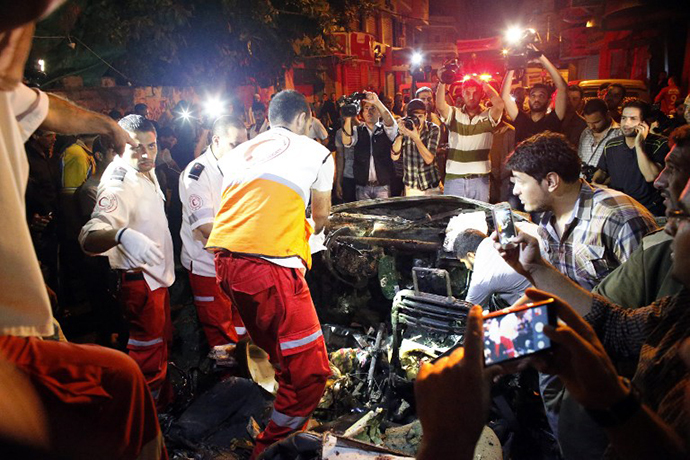 Palestinian rescuers check a car hit by an Israeli air strike killing the driver in Gaza City on July 9, 2014. (AFP Photo / Thomas Coex)