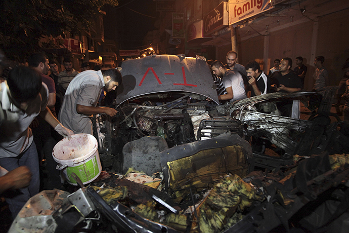 Palestinians inspect the remains of a car which police said was hit in an Israeli air strike in Gaza City July 9, 2014. (Reuters / Ashraf Amrah)