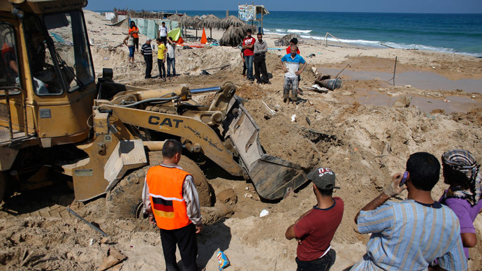 Palestinians use a bulldozer to remove debris of a beach cafe hit last night by an Israeli air strike while people were watching the World Cup semi-final football match, on July 10, 2014 in the southern Gaza Strip city of Khan Yunis.(AFP Photo / Thomas Coex)