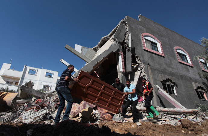 Palestinians carry a door from a destroyed house following what police said was an Israeli air strike in central Gaza Strip July 9, 2014.(Reuters / Ashraf Amrah)