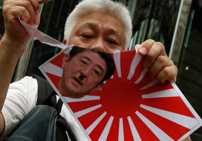 A protester tears an image of a Japanese military flag with a defaced portrait of Japanese Prime Minister Shinzo Abe, outside the Japanese consulate in Hong Kong July 7, 2014.(Reuters / Bobby Yip)